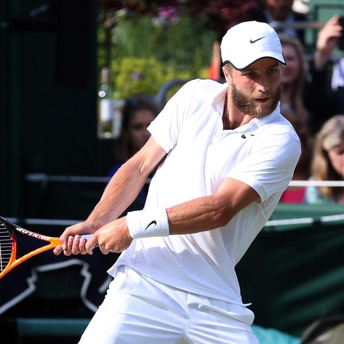 Liam Broady swinging tennis racket.